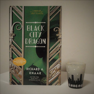 Black City Dragon by Richard A. Knaak paperback next to a shot glass with the skyline of Chicago