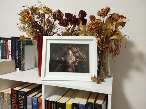 Photo of the art in a white frame on top of my white shelf. There are vases with dried roses around and behind it. The art shows a sexy vampire man with long blonde hair, smirking, holding wine glasses of what is presumably blood.