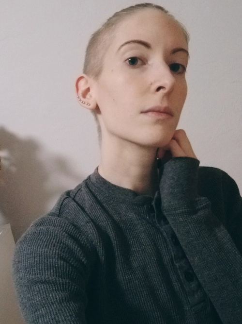 Androgynous photo of myself, not smiling, looking somewhat down and to the side at the viewer. I have dark blonde hair shaved on the side and long on top, tied back. I'm wearing a long-sleeved, textured, gray Henley.